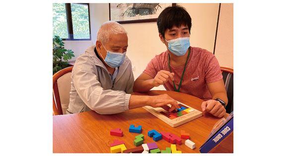 葉梓灝與腦退化症長者一起玩拼砌遊戲。