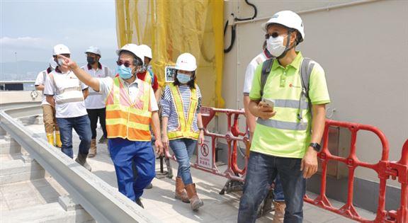 何安誠(中)至今保持巡地盤習慣,周六到地盤視察施工,並推廣工業安全。